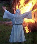 white robed druid before a bonfire