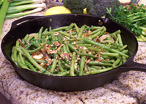 Green Beans in an iron skillet with toasted almonds and fried onions